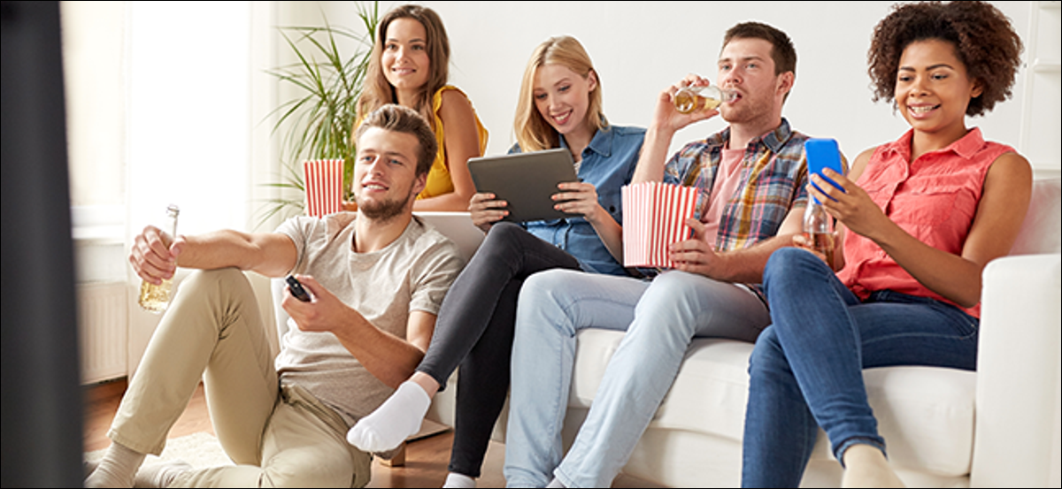 A group of friends eating popcorn and watching TV.