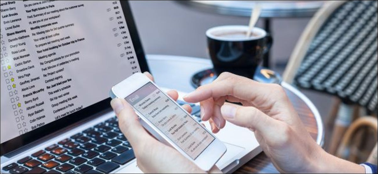 Business person reading email on smartphone and laptop
