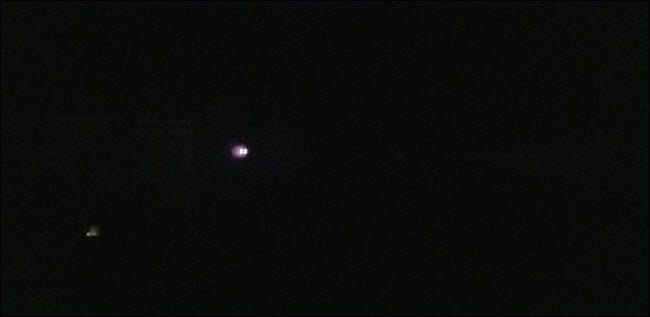 A darkened picture with visible bright lights in the distance.