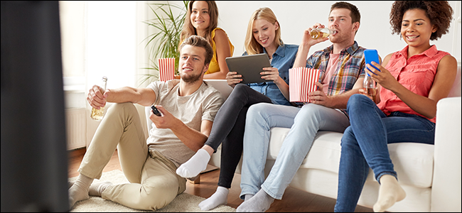 A group of friends watches Netflix on a couch.