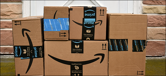 A stack of Amazon boxes near a porch.