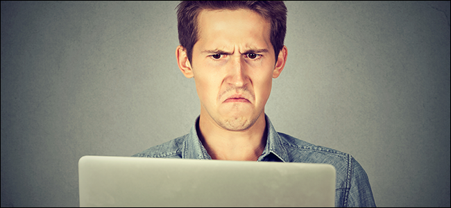A man stares in disgust at his laptop. Evidently, the movie that he bragged about pirating looks like a wad of dirt.