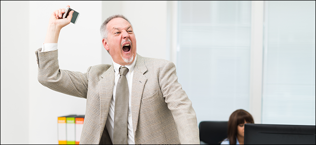 An angry businessman throwing away his phone.