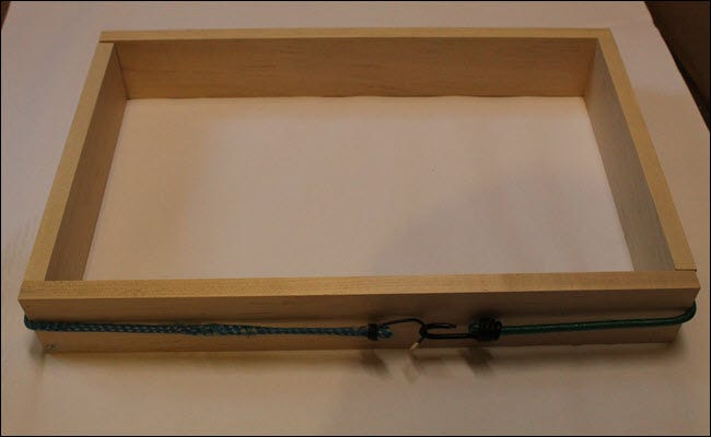 Four pieces of wood arranged in a rectangle with a bungee cord pulling them together.