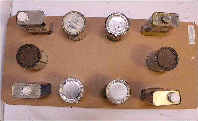 Paint and stain cans sitting atop a flat MDF piece over the box frame.