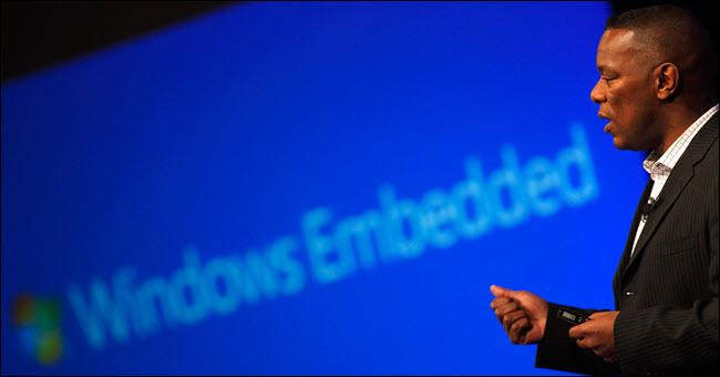 Hombre hablando frente al logo de Windows Embedded.