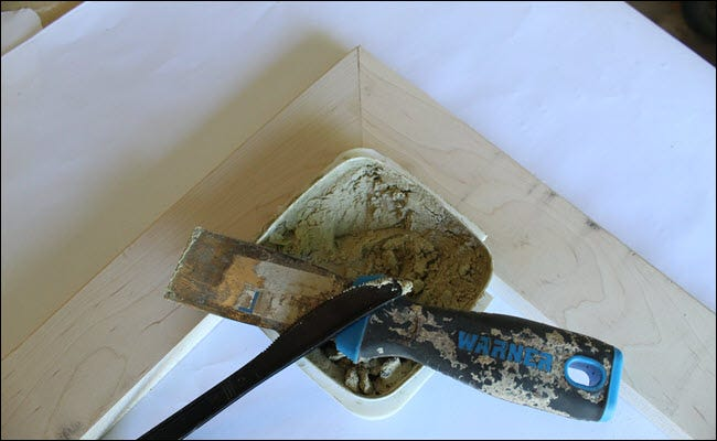 A corner of the frame with wood filler, a putty knife, and a plastic knife.