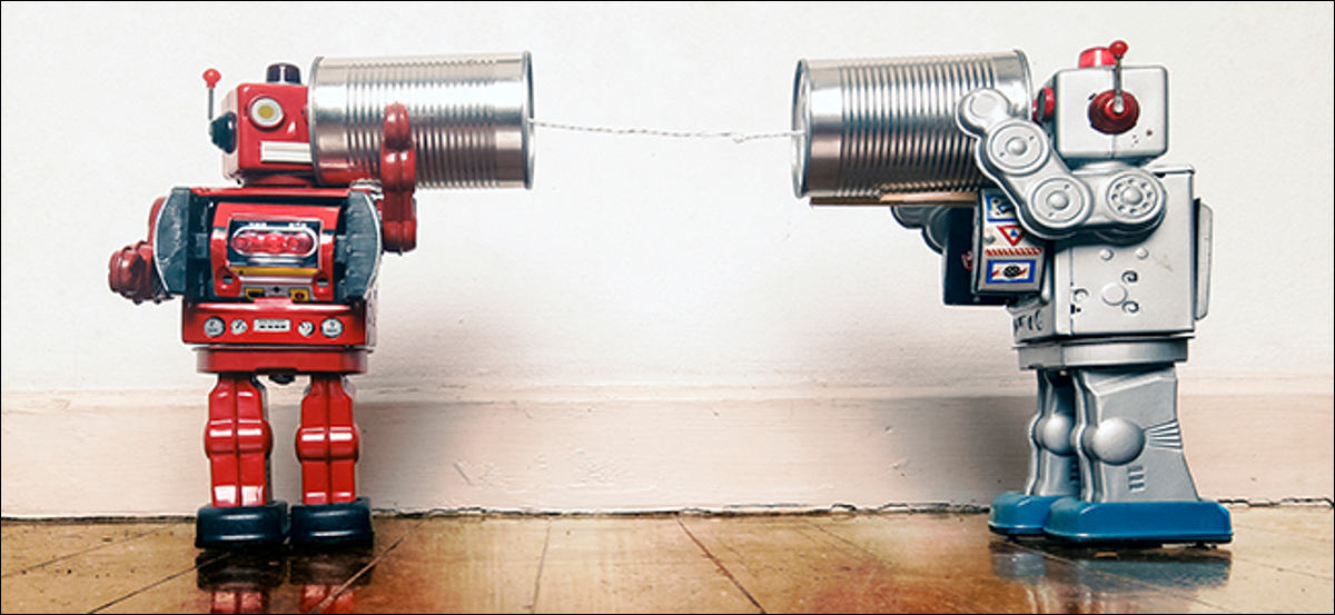 Two robots playing telephone with tin cans.