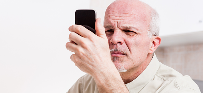 A man stares at his phone, clearly enduring some serious eyestrain.