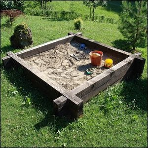 A child's sandbox in a grassy field