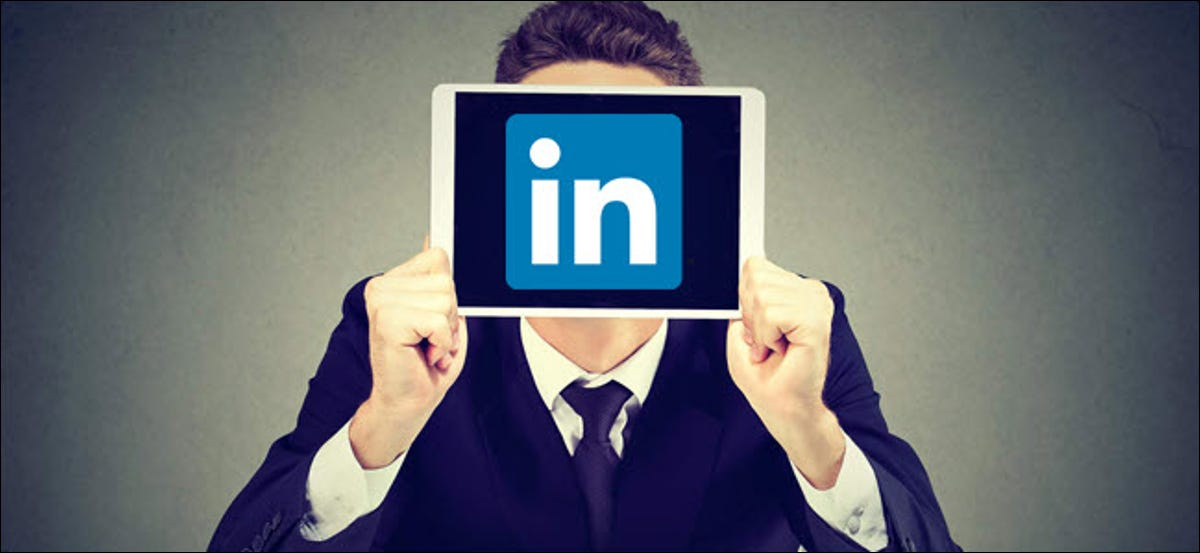 Man in a suit, holding a tablet with LinkedIn logo over his face.