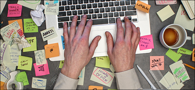A pair of hands working on an extremely messy desk.