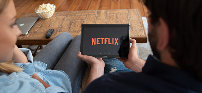 A couple watches Netflix together on a tablet.