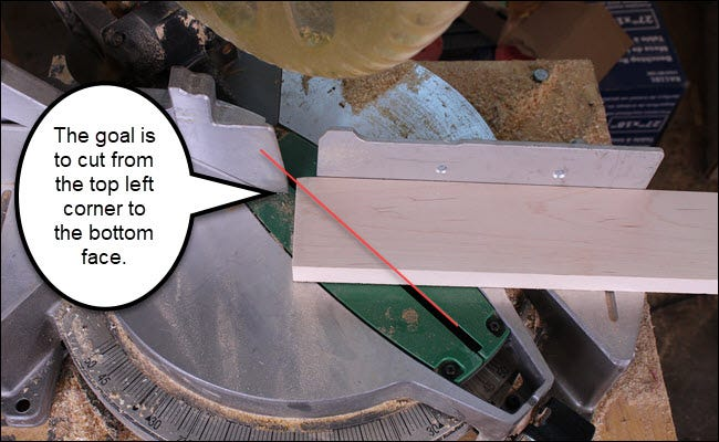 Board on a miter saw, with a 45-degree line drawn on it to show a short cut.
