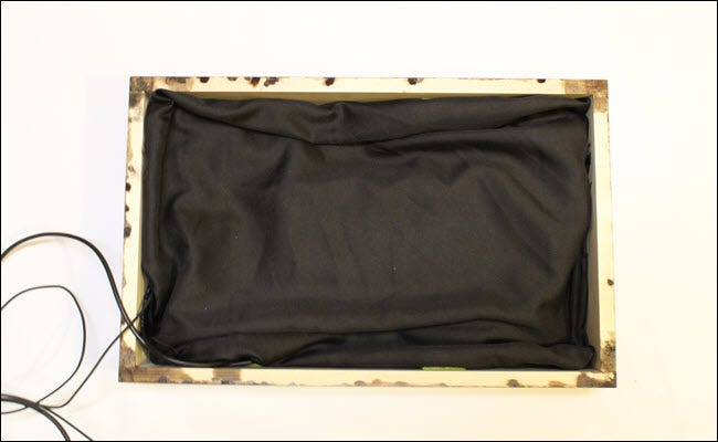 Frame box with draped black cloth.