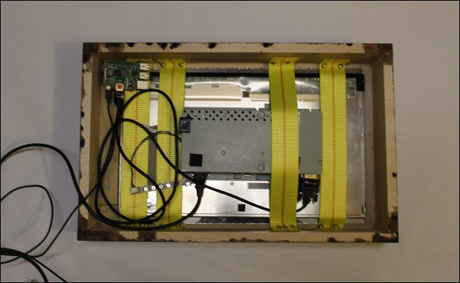 Frame box with strapped monitor and glass and raspberry pi
