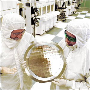 Engineers holding up a wafer of 7mm chips
