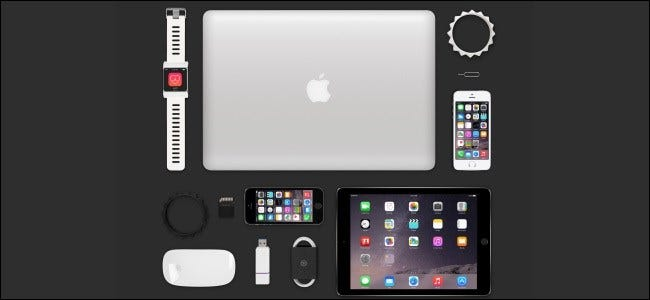 A MacBook, iPad, Apple Watch, several iPhones, and other Apple accessories on a table.