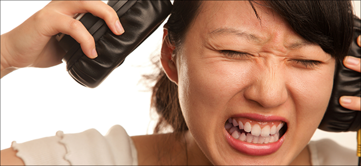 A lady peels off her noise canceling headphones and grimaces from the pain.