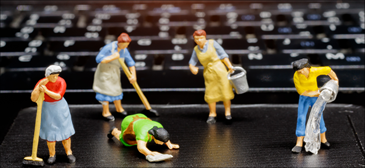 Miniature plastic maids cleaning a laptop