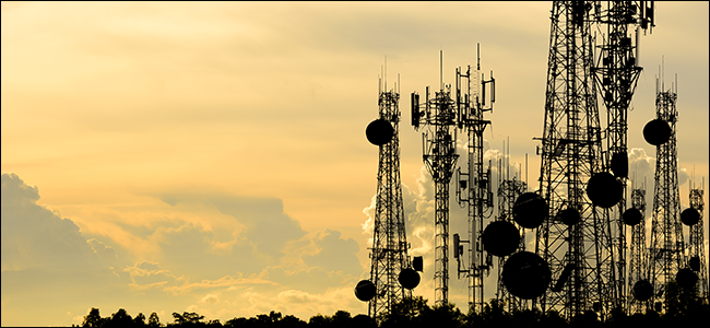 A bunch of broadcasting towers flanked by a beautiful sunset.