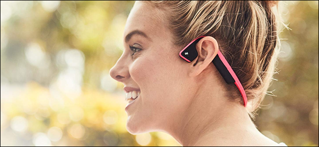 A woman wearing AfterShokz bone conduction headphones. She looks like she's having fun, but she might be telling off a passerby.
