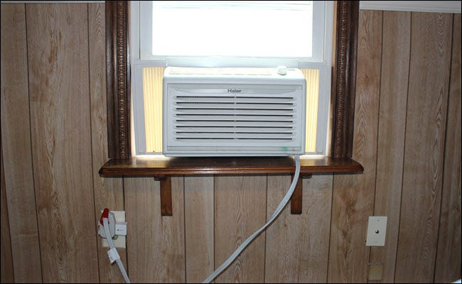 a Window A/C unit connected to a smart plug, which is plugged into an outlet.