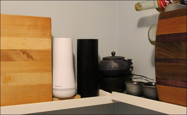 An Echo next to a tea pot, a SimpliSafe, and two cutting boards.