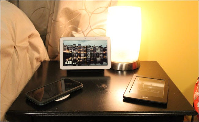 A Nest Hub, wireless charger, lamp with smart bulb, and kindle.