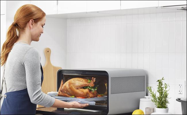 Mujer sacando un pavo de cocción de un horno inteligente de junio