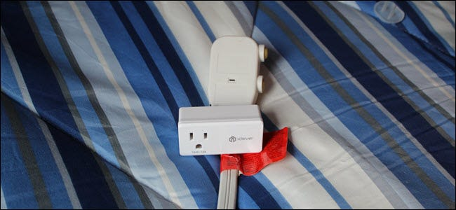 An iClever smart plug on top of an A/C units plug, over a blue blanket.