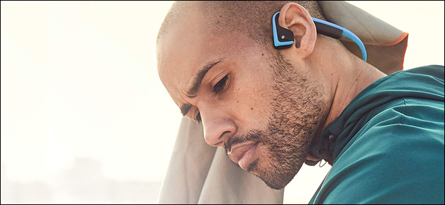 A man wearing AfterShokz bone conduction headphones. He looks very thoughtful. Perhaps he's listening to a podcast.