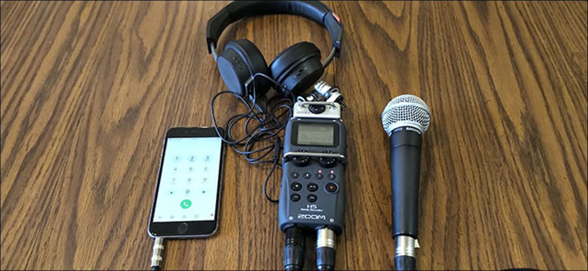 An iPhone, Shure SM58 Microphone,and headphones all connected to an H5 Zoom recorder, lying on a table.