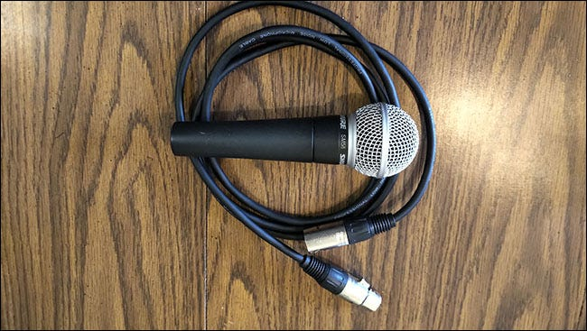 A Shure SM58 Microphonelying on top of an AmazonBasics XLR cable on a table.