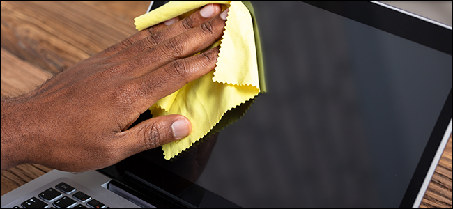 A man's hand cleaning a laptop screen with a microfiber cloth.