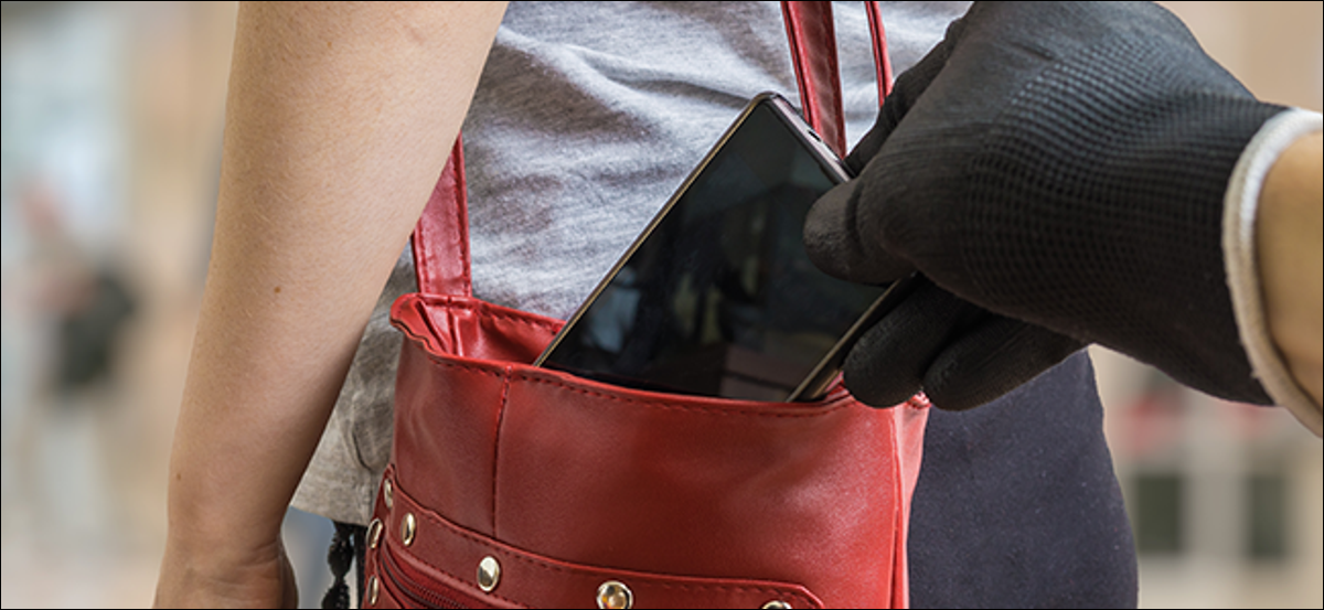 A gloved hand stealing a phone from a purse.
