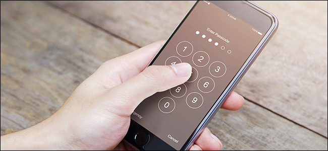 A hand typing a passcode into a phone.