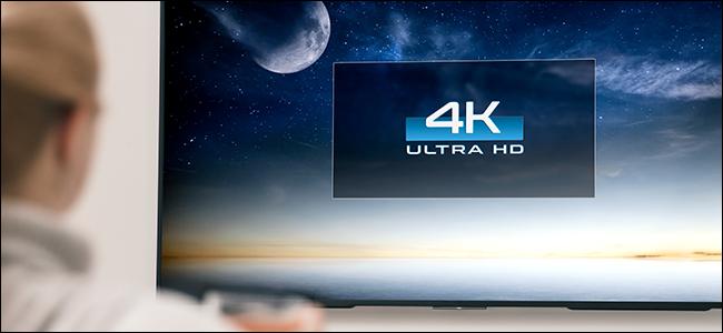 Persona que mira un televisor de pantalla grande de 4K.