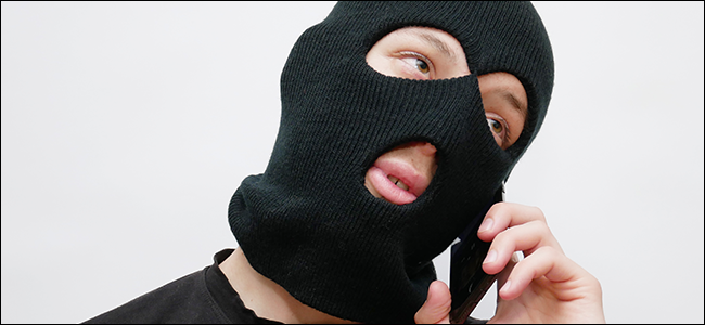 A man in a ski mask talking on a phone.