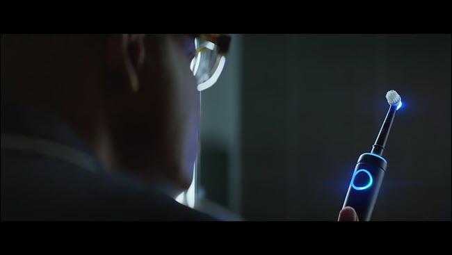 Hombre del comercial de Alexa mirando su cepillo de dientes Echo iluminado.