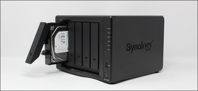 A Synology NAS with one hard drive partially removed.