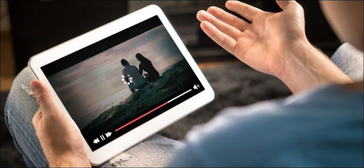 Man's hands holding a tablet showing buffering video.