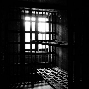 Black and white photograph of the interior of an old jail cell