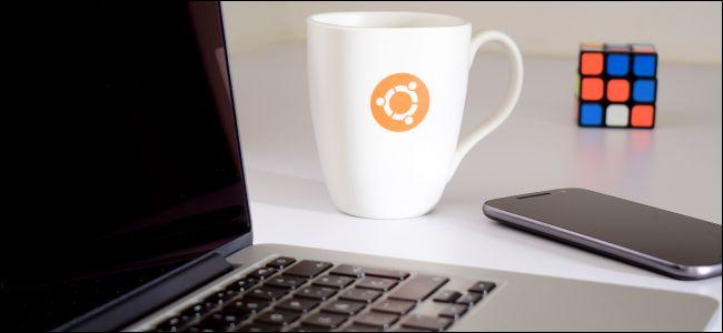 Ubuntu mug next to a laptop, phone, and Rubik's Cube.