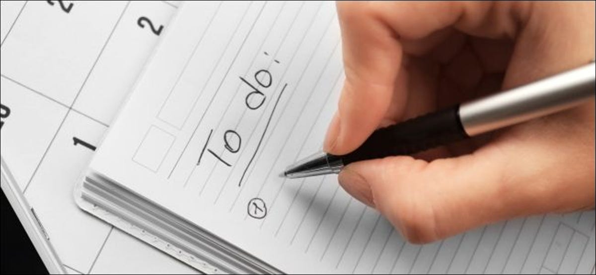 Hand writing a to-do list in a notebook.
