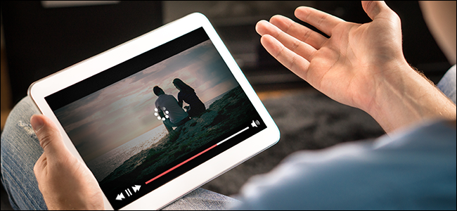 "A man's hands holding a tablet displaying a ""loading"" icon on a video."