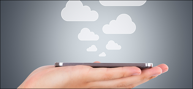 A hand holding a phone as clouds rise out of it, symbolizing files being saved to the cloud.