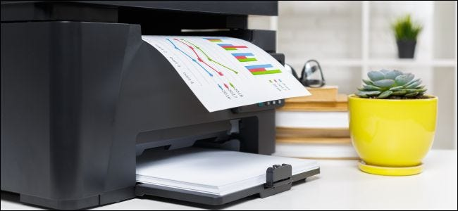 A printer sitting on a desk, printing out a sheet of paper with a bar graph on it.