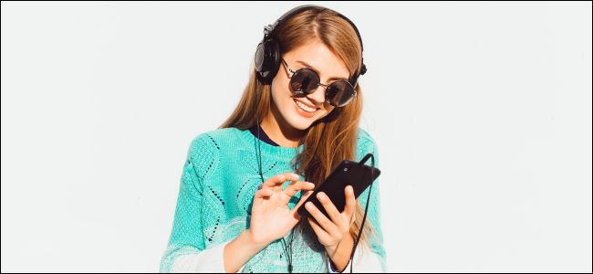 Woman wearing headphones and tapping at an iPhone