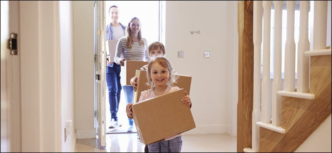 A happy family carrying boxes in a house.